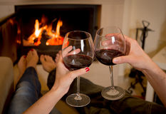 Couple drinking wine in front of a fire Royalty Free Stock Image