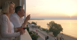 Couple drinking wine and looking at resort from balcony stock video footage