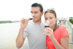Couple drinking wine by river Stock Photography