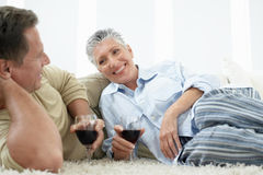 Couple Drinking Wine On Rug In Home Stock Photo