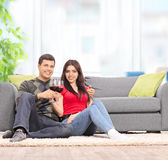 Couple drinking wine seated by a sofa at home Royalty Free Stock Images