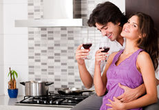 Couple drinking wine in their kitchen Royalty Free Stock Photography