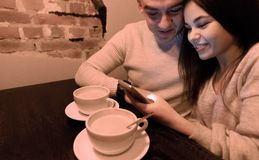 Couple Drinks Coffee and Discuss News on the Phone. Winter Concept stock image