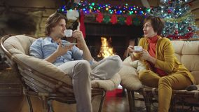 Couple drinks coffee and talks in Christmas night stock footage