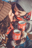 Couple drinks hot tea in winter park Royalty Free Stock Images