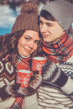 Couple drinks hot tea in winter park Stock Images