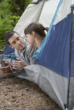 Couple With Drinks Lying In Tent Entrance Royalty Free Stock Image