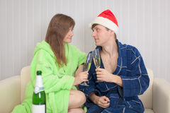 Couple drinks sparkling wine sitting on sofa Royalty Free Stock Photography