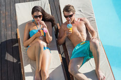 Couple with drinks on sun loungers by swimming pool Royalty Free Stock Images