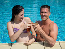 Couple with drinks in the sund at pool Stock Photography