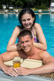 Couple with drinks at swimming pool Royalty Free Stock Photography