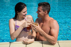 Couple with drinks at swimming pool Stock Image