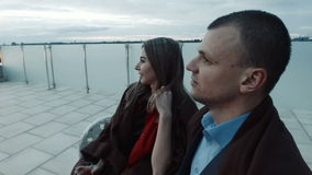 Couple with drinks talking, watching sunset stock footage