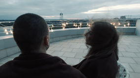 Couple with drinks talking, watching sunset. Young couple with drinks sitting on balcony and talking while watching evening sky stock footage