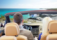 Couple driving in cabriolet car over sea shore. Drive, auto trip, travel, tourism and people concept - close up of couple driving in cabriolet car from back over Royalty Free Stock Photography