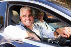 Couple driving car. Lovely middle aged couple driving a car royalty free stock photography
