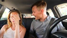 Couple driving in the car, a man and a woman in the car through the streets of the city and quarrel. Shout at each other stock video