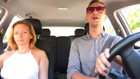 Couple driving in the car, a man and a woman ride together in the car through the streets of the city and look around stock video