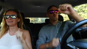 Couple driving in the car, a man and a woman riding together in the car through and dancing while sitting in the car. 4K stock video