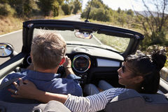 Couple driving in car, woman looks at her partner, back view Stock Photos