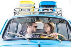 Couple driving car. Young happy couple of tourists driving car and looking at each other isolated on white royalty free stock images