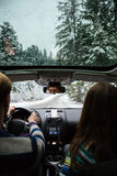 Couple driving in modern car at winter forest royalty free stock photo