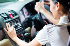 Couple driving new car, she is turning on the radio Royalty Free Stock Photography