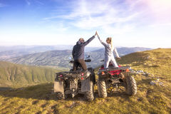 Couple driving off-road with quad bike or ATV Stock Image