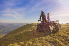 Couple driving off-road with quad bike or ATV.  Royalty Free Stock Images