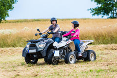Couple driving off-road with quad bike or ATV Stock Images