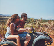 Couple driving off-road with quad bike. Side view of young men and women riding on a quad bike on a summer holiday. Couple enjoying holidays on a quad bike in Royalty Free Stock Photos