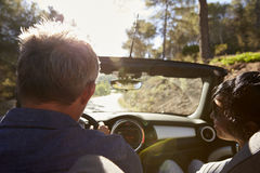 Couple driving in open top car, rear passenger point of view Royalty Free Stock Photo