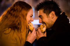 Couple duel - eating together in street Royalty Free Stock Photos