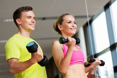 Couple with dumbbells exercising in gym. Sport, fitness and people concept - couple with dumbbells exercising in gym royalty free stock images