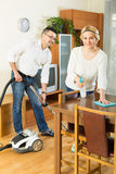 Couple dusting and hoovering Stock Photography