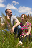 Couple with e-cigarette in a meadow. Adult couple with e-cigarette in a meadow stock images