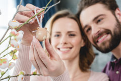 Couple with easter decoration. Close-up view of smiling young couple putting decorative easter egg on branch royalty free stock images