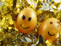 Couple of easter eggs with drawing happy smiling, on golden tuft Royalty Free Stock Photos