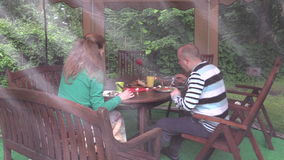 Couple eat backed meat at table with candle in garden gazebo. stock video