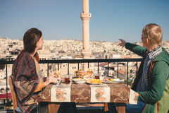 Couple eat traditional turkish breakfast on rooftop with city vi Stock Image