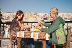 Couple eat traditional turkish breakfast on rooftop with city vi stock photo
