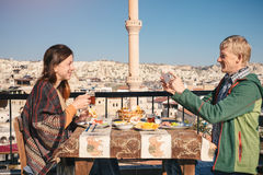 Couple eat traditional turkish breakfast on rooftop with city vi Royalty Free Stock Images