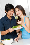 Couple Eating. An attractive asian couple having a healthy salad in their kitchen at home stock image
