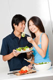 Couple Eating. An attractive asian couple having a healthy salad in their kitchen at home stock photos