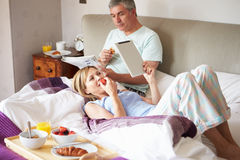 Couple Eating Breakfast In Bed With Paper And Digital Tablet. Lying Down Relaxing royalty free stock photo