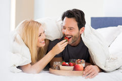 Couple eating breakfast on bed. Portrait of a happy women feeding strawberry to men for breakfast. Young smiling couple eating breakfast on bed. Happy young Royalty Free Stock Images