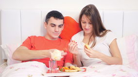 Couple eating breakfast in the bed. Young couple eating breakfast of pancakes and strawberries in the bed stock footage