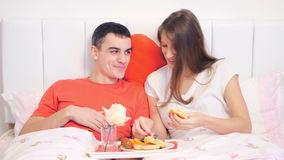 Couple eating breakfast in the bed. Young couple eating breakfast of pancakes and strawberries in the bed stock video