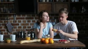 Couple eating breakfast in the morning in kitchen stock video footage