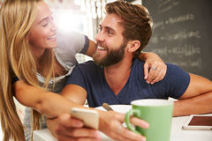 Couple Eating Breakfast Using Digital Tablet And Phone Stock Photos